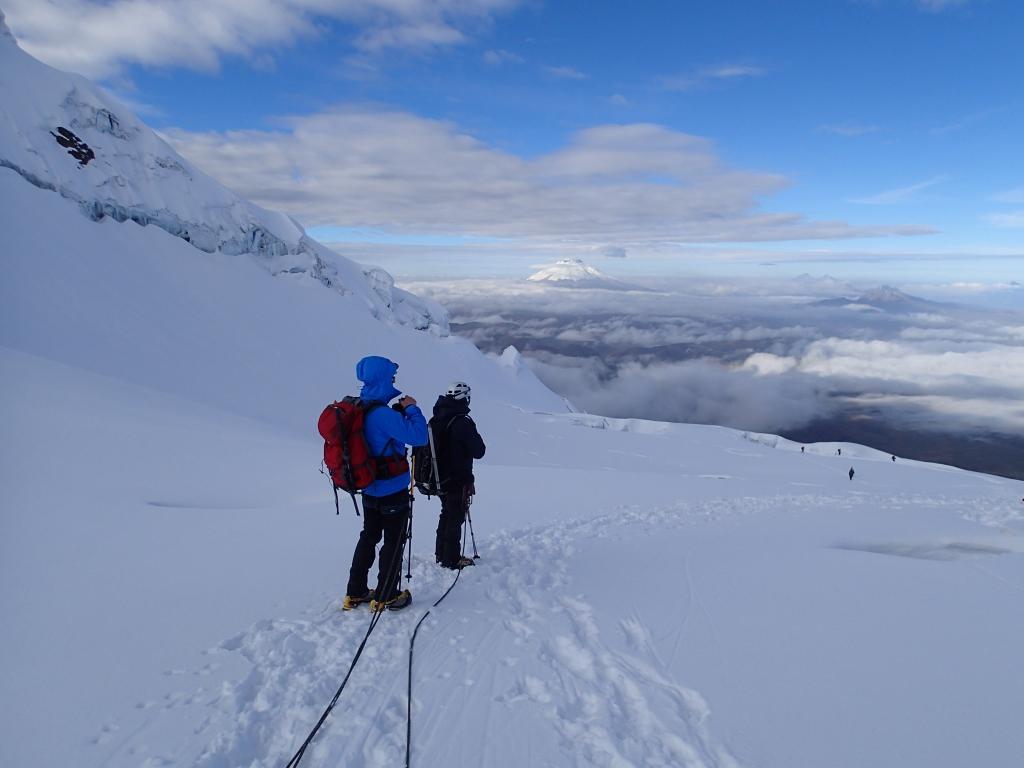 Billede af bjergbestigere på vej ned ad Antisana med Cotopaxi i horisonten